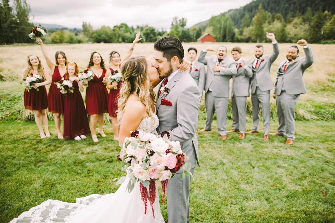 Bride and groom kissing with wedding party cheering