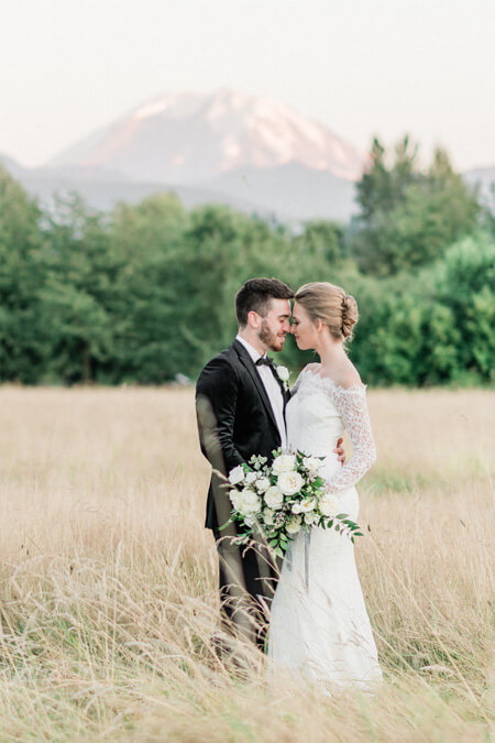Bride and groom in hayfield with Mount Rainier view at Mount Peak Farm Wedding and Event Venue