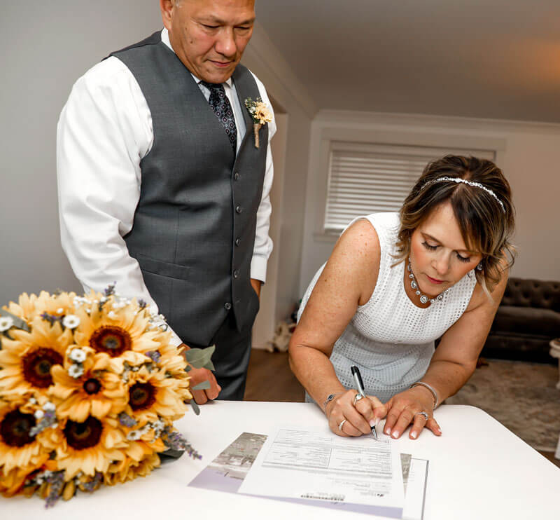 Bride and groom signing next to sunflower bouquet