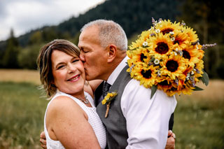 Bride and groom kiss with sunflower bouquet