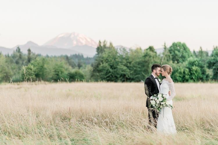 French Countryside Wedding Inspiration Bride and groom in hayfield with Mount Rainier view.