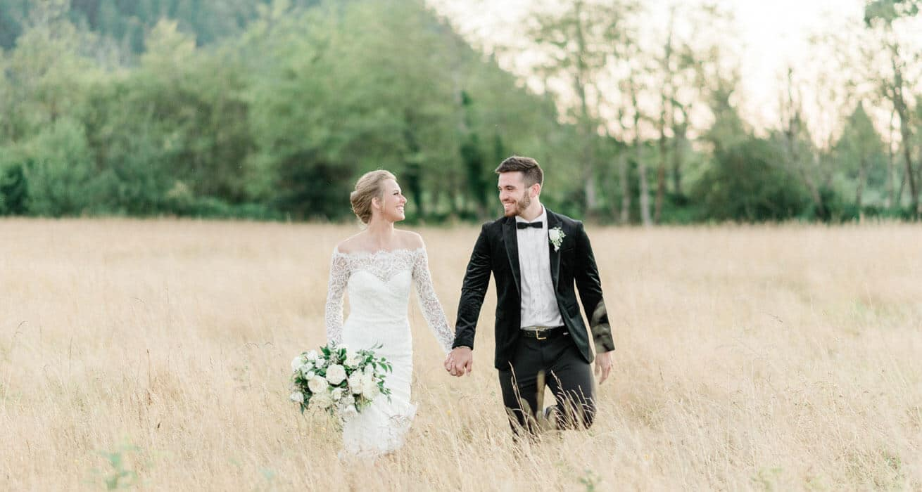 Bride and groom walking in hayfield at Mount Peak Farm