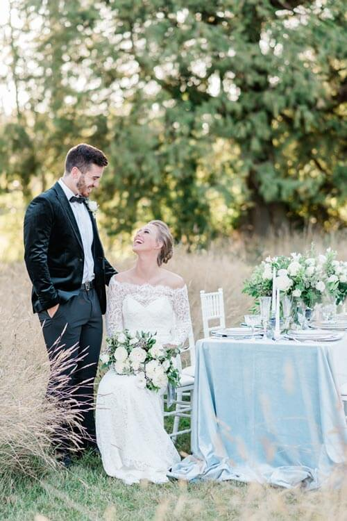 French Countryside Wedding Inspiration bride and groom at reception table in field