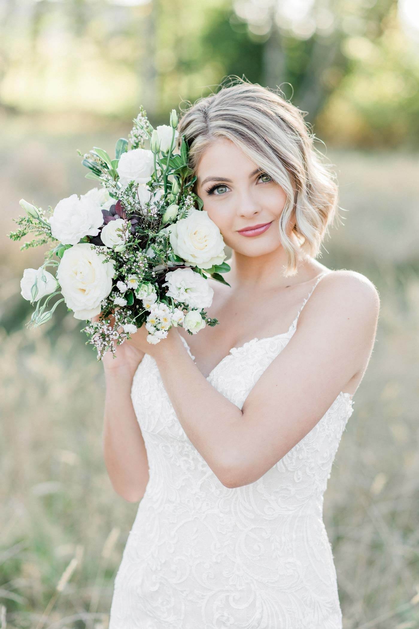 Romantic blush wedding bride in field with bridal bouquet