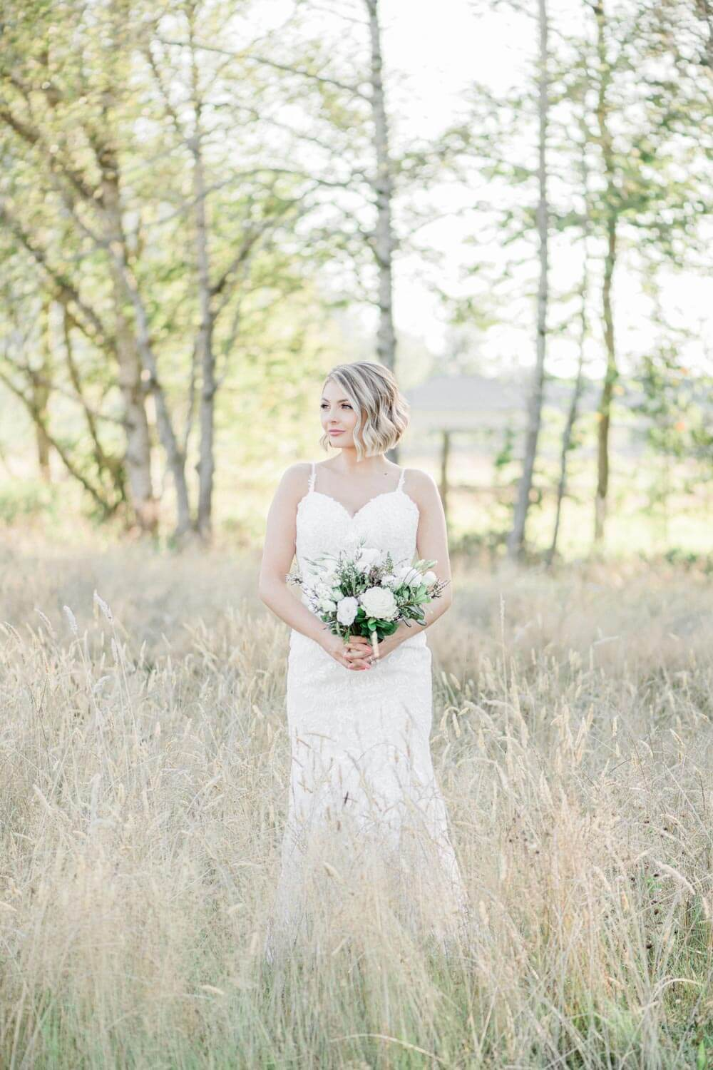 Bride in hayfield with bouquet at Mount Peak Farm