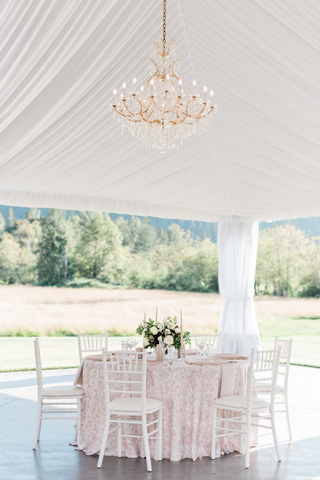 Romantic blush wedding table under chandeliers