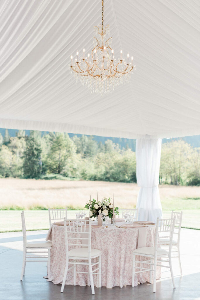 Romantic blush wedding table under chandeliers at Mount Peak Farm