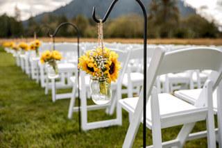 Wedding ceremony aisle with shepherd hooks holding mason jars with sunflower bouquets