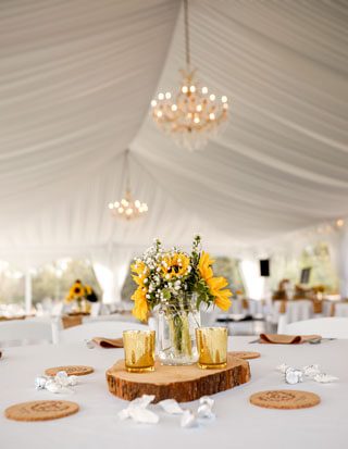 Reception tent with sunflowers and chandeliers