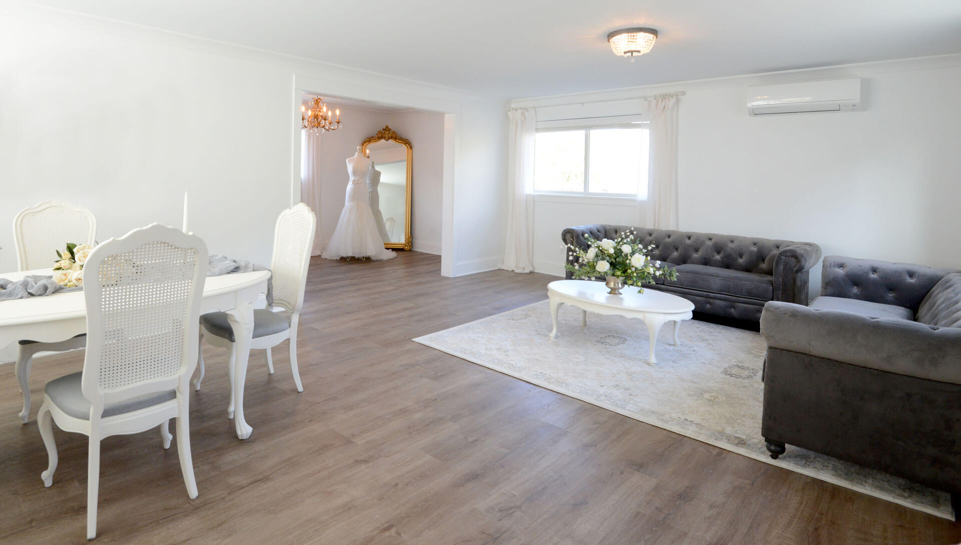 Bridal cottage with gray velvet sofas, french country dining set, and full length gold mirror