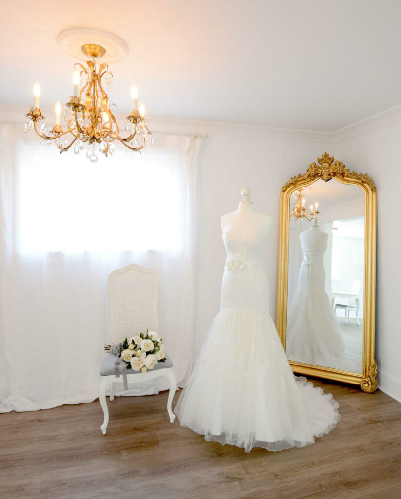 Bridal cottage at Mount Peak Farm. Wedding dress with full-length gold mirror and gold chandelier