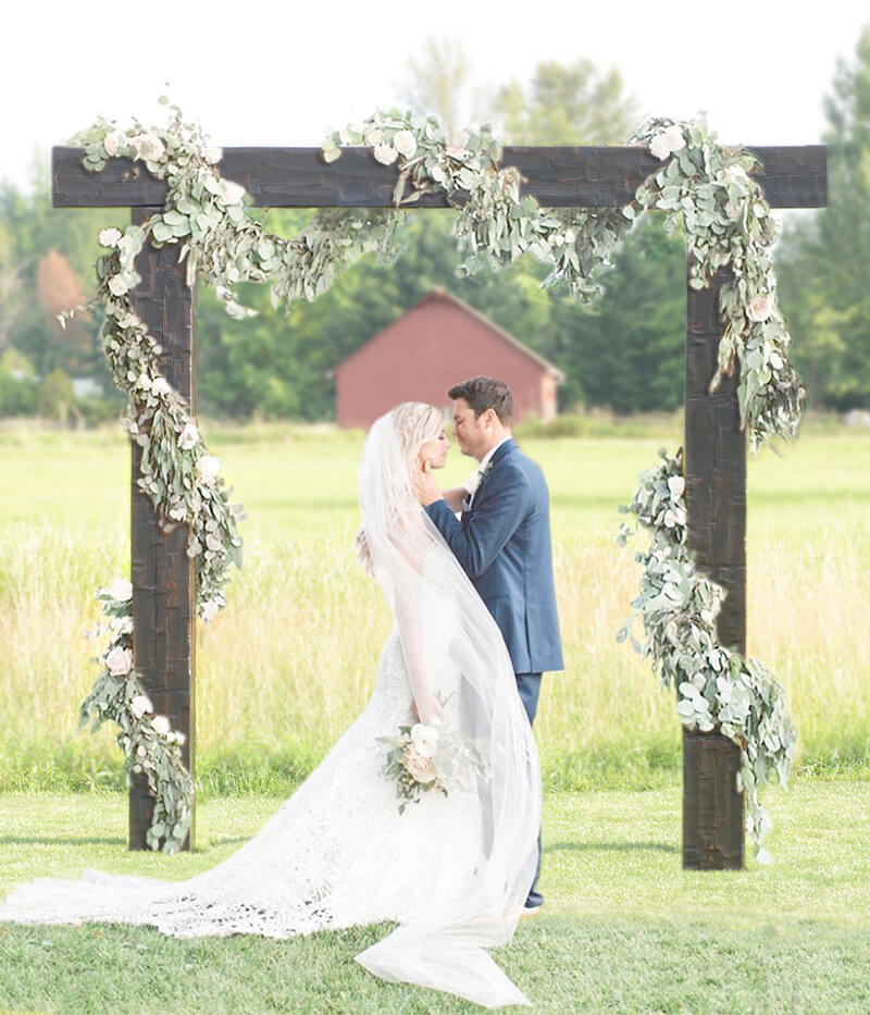 Rustic wood arbor with bride and groom