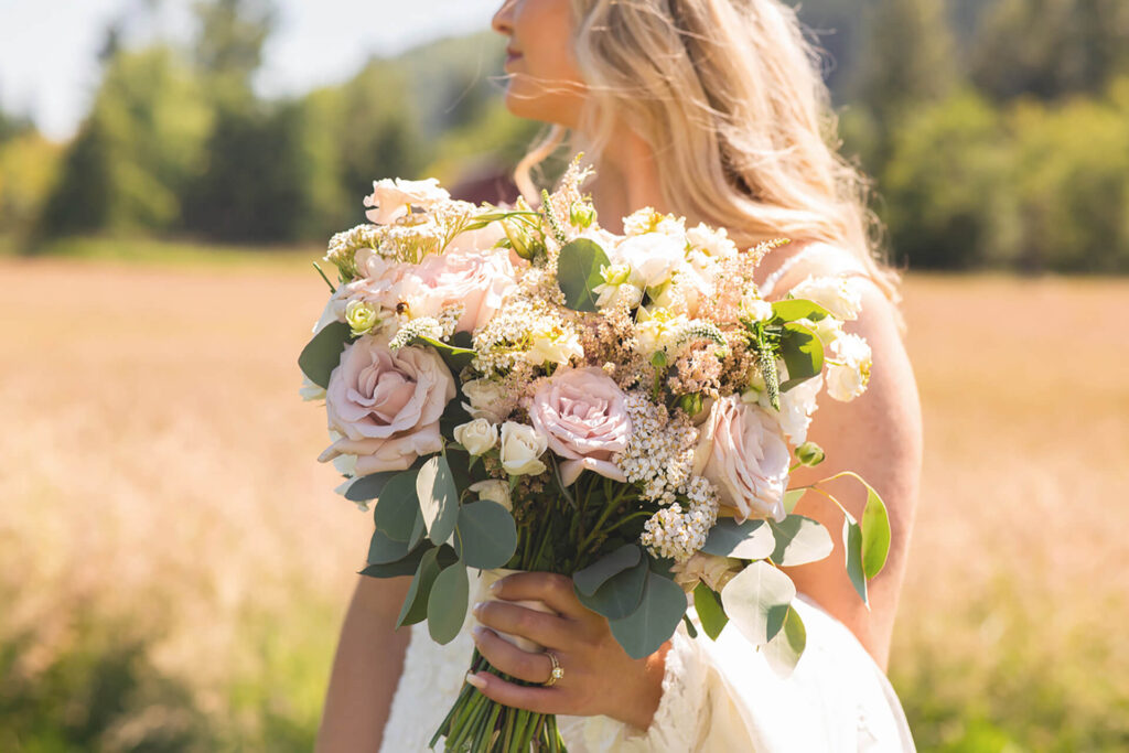 Bride holding bouquet in field at Mount Peak Farm