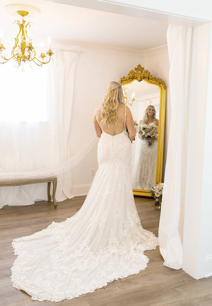 Bride looking in gold mirror in bridal cottage at Mount Peak Farm