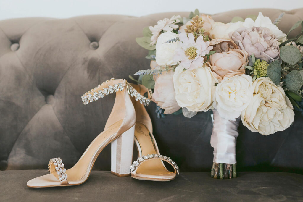 Glam shoes and bouquet on velvet sofa