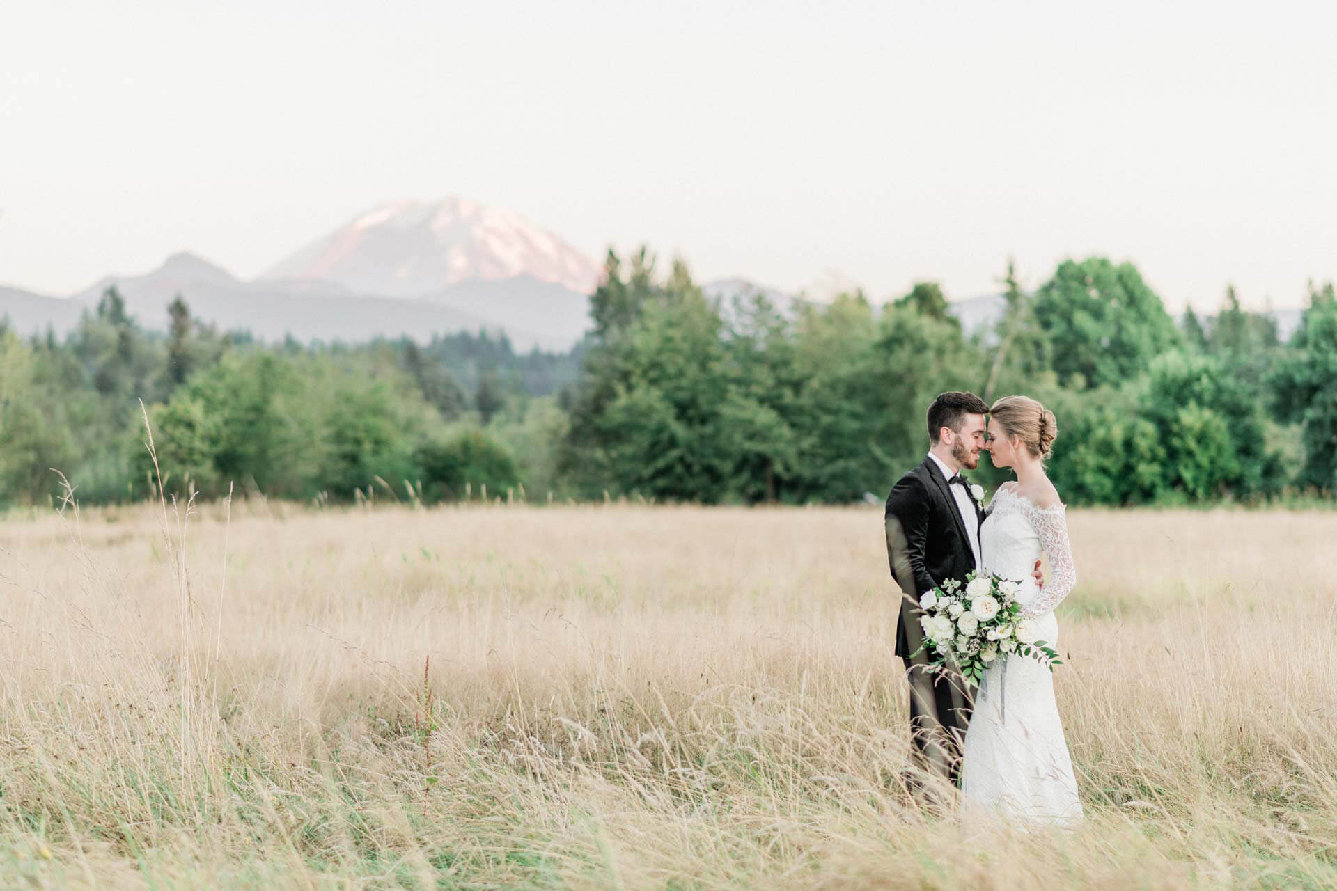 Couple in hayfield with Rainier at Mount Peak Farm