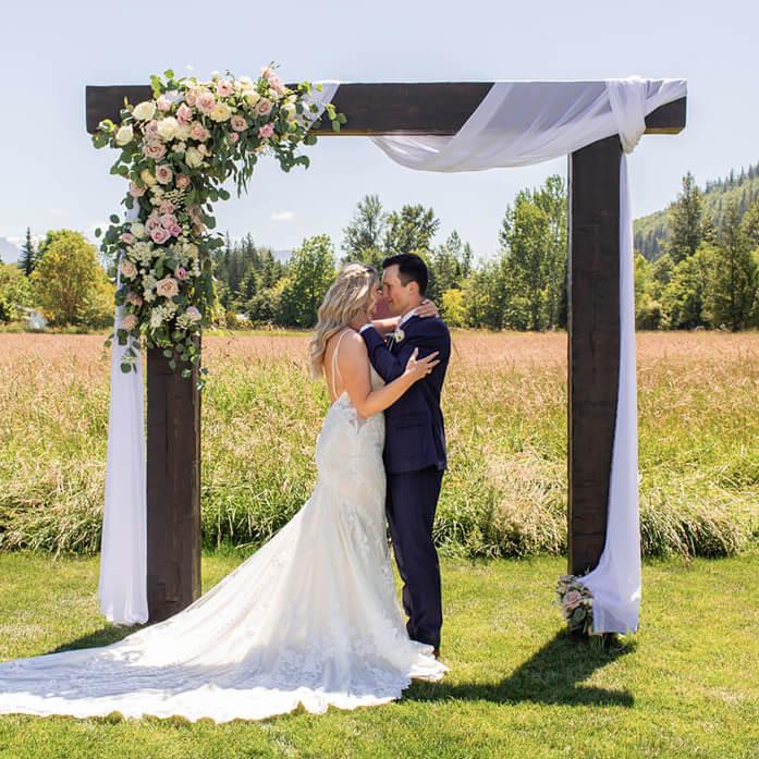 Bride and groom kissing under arbor at Mount Peak Farm